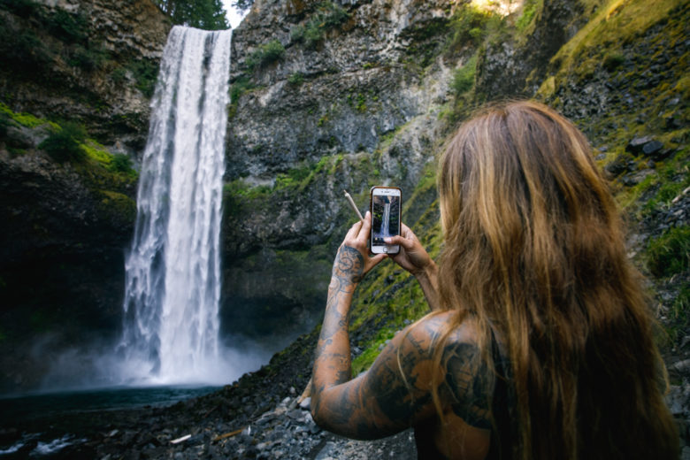 Cute girl smoking cannabis by waterfall